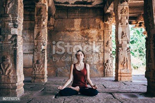 Woman doing yoga in Vishnu temple in Hampi, India