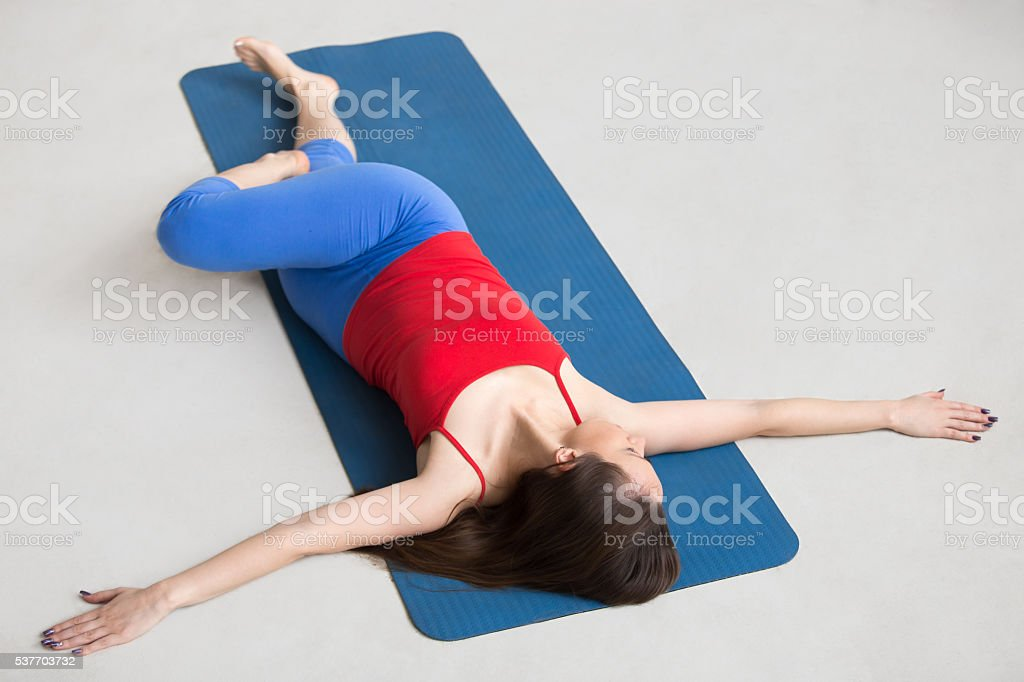Yoga Indoors: Revolved Abdomen Pose stock photo