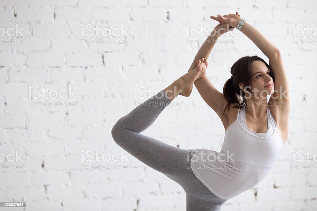 Yoga Indoors: Variation of Natarajasana stock photo