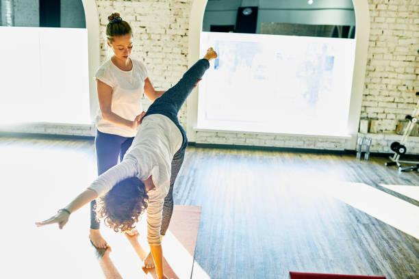 Yoga instructor assisting student stock photo