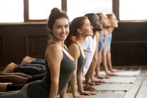 Yoga instructor looking at camera doing exercise at group training Smiling yoga instructor looking at camera doing fitness stretching backbend exercise together teaching multi-ethnic diverse people at group training class in studio, sporty yogi fit teacher portrait upward facing dog position stock pictures, royalty-free photos & images