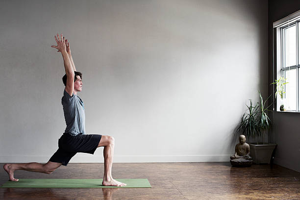 Yoga Instructor A male yoga instructor does a pose at an indoor yoga studio. yoga instructor stock pictures, royalty-free photos & images