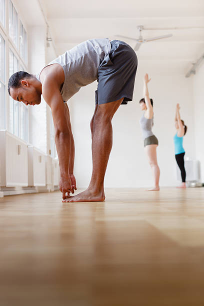 Yoga Instructor with Students Yoga instructor leading a class of students. Instructor is in forward bending pose while students are doing a Upward Salute pose. Vertical shot. touching toes stock pictures, royalty-free photos & images