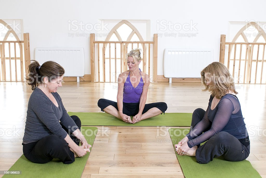 Yoga instructor with two students royalty-free stock photo