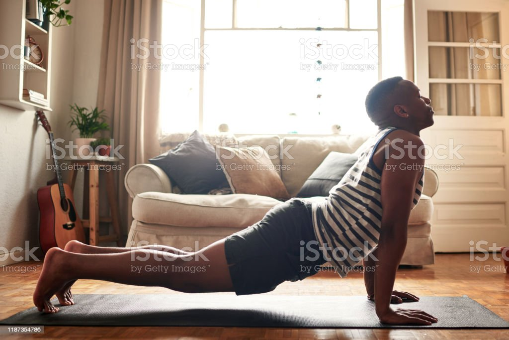 Yoga is for everyone Shot of a young man practising yoga at home during the day 20-29 Years Stock Photo
