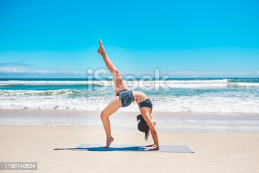Shot of a young woman practising yoga at the beach