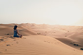 Young woman meditating in the desert, at the Wildlife resort during sunset