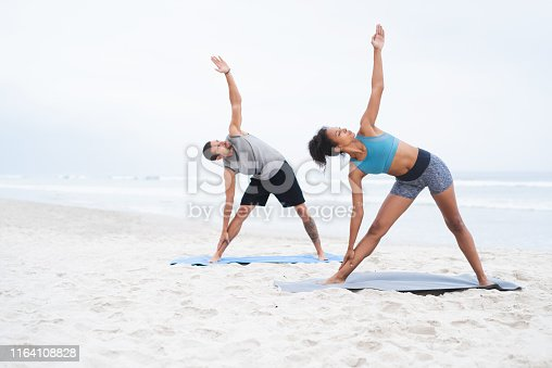 Shot of a young man and woman practising yoga together at the beach