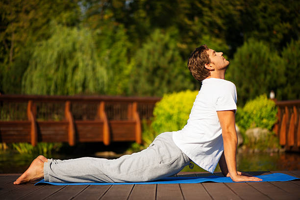 Yoga man in cobra pose Young man practising yoga and standing in cobra pose with a beautiful green scenery of park on background cobra pose stock pictures, royalty-free photos & images