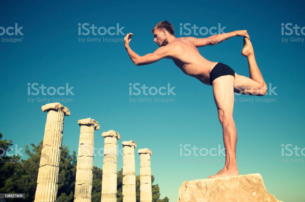 Yoga Man Stretching in front of Ancient Greek Columns royalty-free stock photo