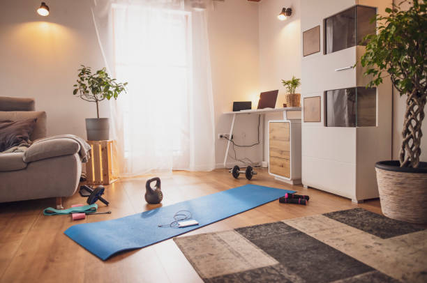 Yoga mat and exercise equipment in living room stock photo