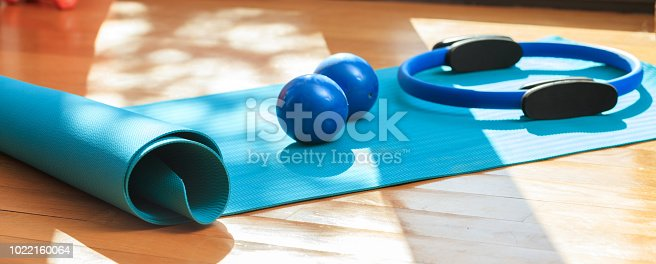 istock Yoga mat and exercise weights on wooden floor 1022160064