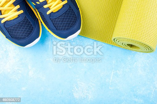 637596492 istock photo Yoga mat and sport shoes on blue background. Concept healthy lifestyle, sport and diet. Sport equipment 692503772