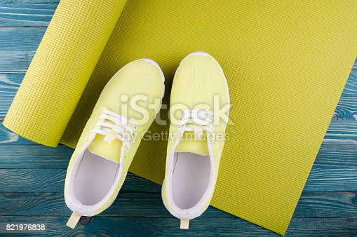 637596492istockphoto Yoga mat and sport shoes on wooden background. Healthy lifestyle, yoga, sport concept. Copy space 821976838