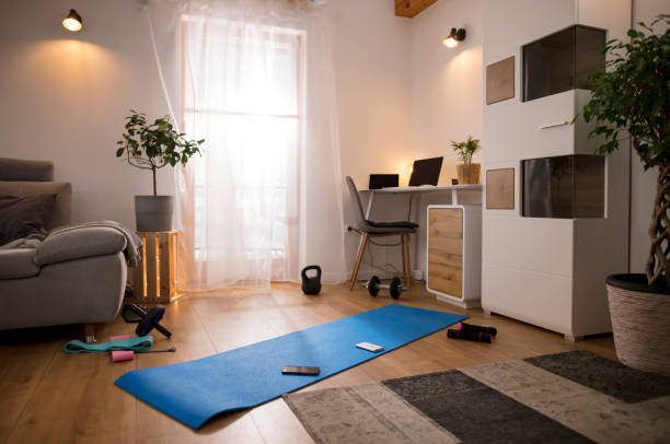 Yoga mat and weights on living room floor stock photo