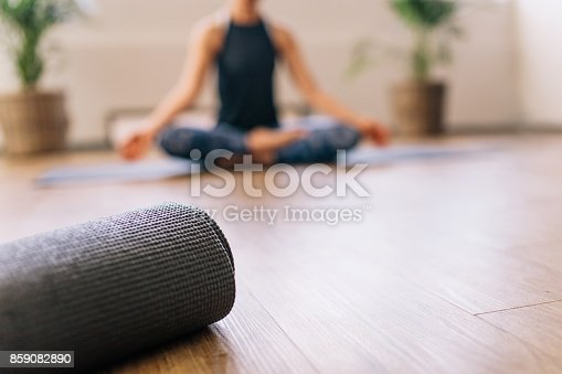 istock Yoga mat in fitness center with woman meditating at back 859082890