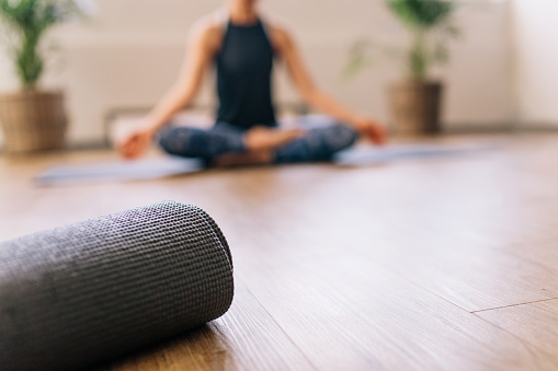 Close up of rolled yoga mat in fitness center and blurred woman at the back in lotus yoga pose. Fitness mat on floor with woman practising yoga in background.