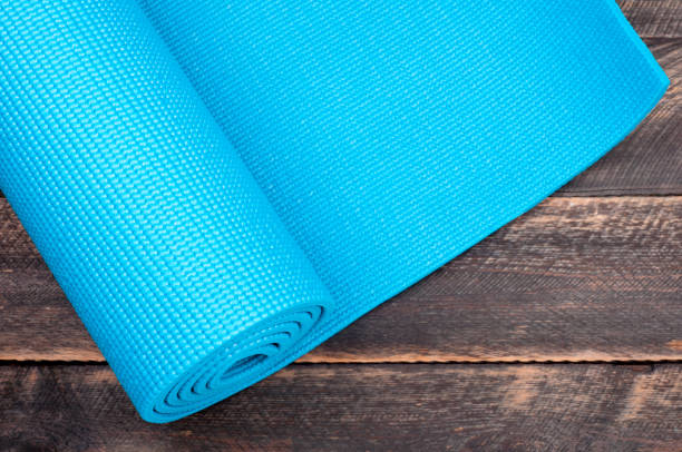 Yoga mat on a wooden background. Equipment for yoga. Concept healthy lifestyle. Copyspace. Selective focus stock photo