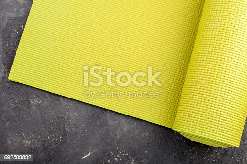 637596492istockphoto Yoga mat on dark background. Equipment for yoga. Concept healthy lifestyle, sport and diet. Copyspace 692503832