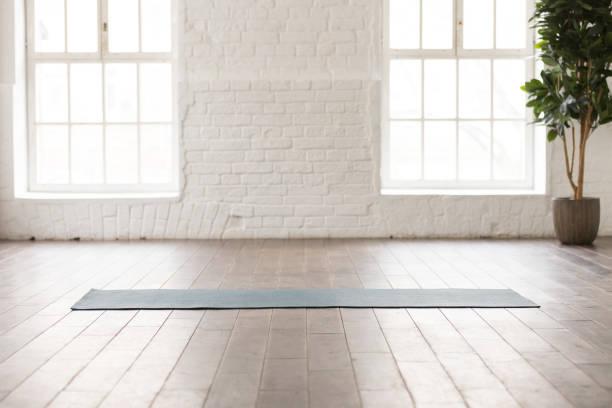 yoga-matte auf natürlichem holzboden im leeren raum - meditationsräume stock-fotos und bilder