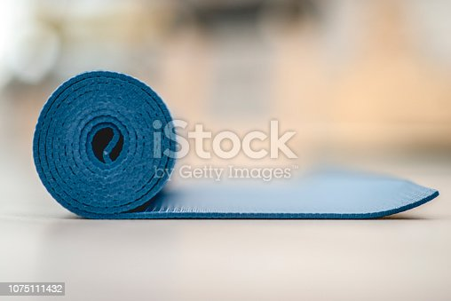 A blue yoga mat is slightly unrolled on a wooden floor.
