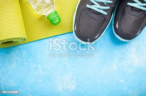 637596492 istock photo Yoga mat, sport shoes and bottle of water on blue background. Concept healthy lifestyle, sport and diet. Sport equipment 692503688