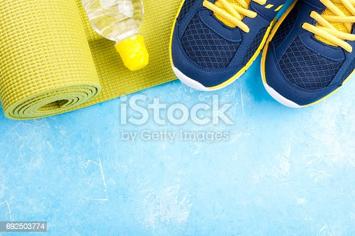637596492 istock photo Yoga mat, sport shoes and bottle of water on blue background. Concept healthy lifestyle, sport and diet. Sport equipment 692503774