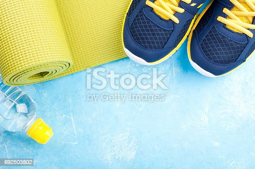 637596492 istock photo Yoga mat, sport shoes and bottle of water on light background. Concept healthy lifestyle, sport and diet. Sport equipment 692503802