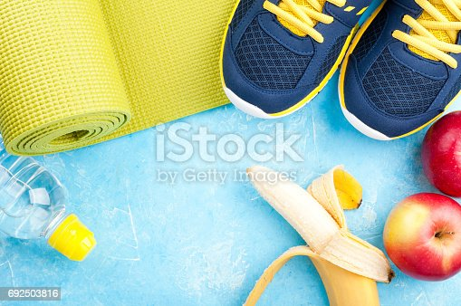 637596492 istock photo Yoga mat, sport shoes, apples, banana, bottle of water on dark background. Concept healthy lifestyle, healthy eating, sport and diet. Sport equipment 692503816