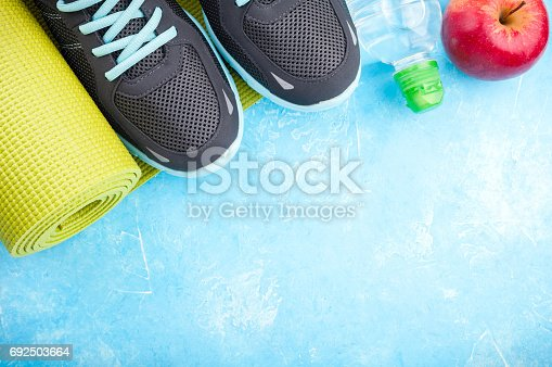 637596492istockphoto Yoga mat, sport shoes, apples, bottle of water on blue background. Concept healthy lifestyle, healthy food, sport and diet. Sport equipment 692503664