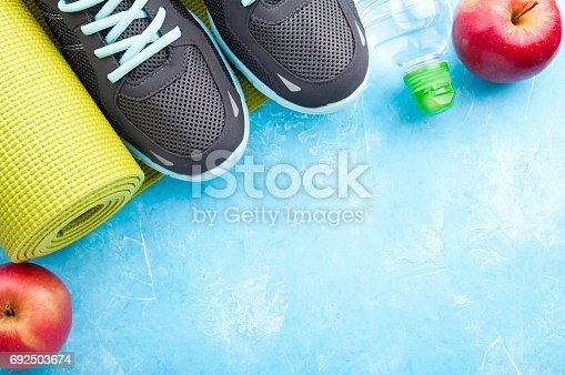 637596492 istock photo Yoga mat, sport shoes, apples, bottle of water on blue background. Concept healthy lifestyle, healthy food, sport and diet. Sport equipment 692503674