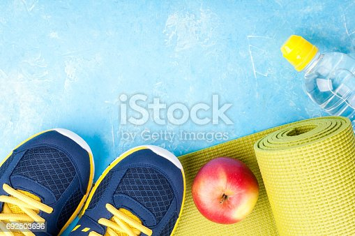 637596492 istock photo Yoga mat, sport shoes, apples, bottle of water on blue background. Concept healthy lifestyle, healthy food, sport and diet. Sport equipment 692503696