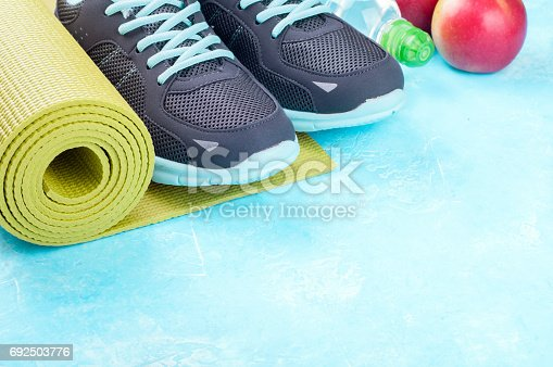 637596492 istock photo Yoga mat, sport shoes, apples, bottle of water on blue background. Concept healthy lifestyle, healthy food, sport and diet. Sport equipment 692503776