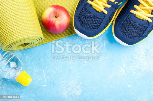 637596492istockphoto Yoga mat, sport shoes, apples, bottle of water on dark background. Concept healthy lifestyle, healthy food, sport and diet. Sport equipment 692503814