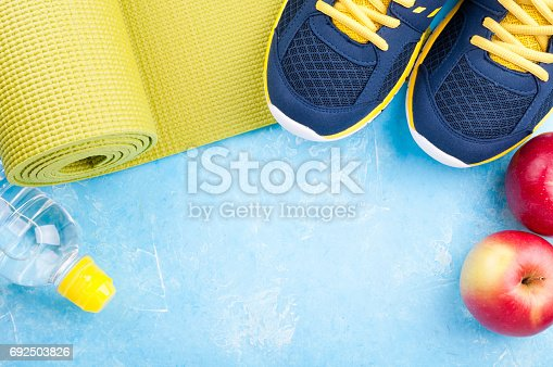 637596492istockphoto Yoga mat, sport shoes, apples, bottle of water on dark background. Concept healthy lifestyle, healthy food, sport and diet. Sport equipment 692503826