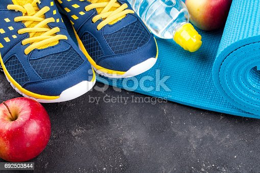 637596492 istock photo Yoga mat, sport shoes, apples, bottle of water on dark background. Concept healthy lifestyle, healthy eating, sport and diet. Sport equipment 692503844