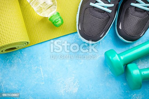 istock Yoga mat, sport shoes, dumbbells and bottle of water on blue background. Concept healthy lifestyle, sport and diet. Sport equipment 692503662