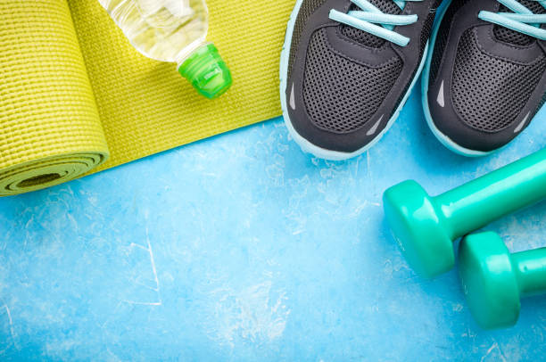 Yoga mat, sport shoes, dumbbells and bottle of water on blue background. Concept healthy lifestyle, sport and diet. Sport equipment stock photo