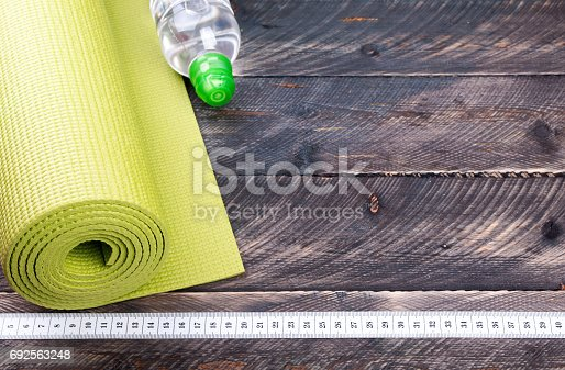 637596492 istock photo Yoga mat, water bottle and centimeter on a wooden background. Equipment for yoga. oncept  healthy lifestyle. Selective focus 692563248