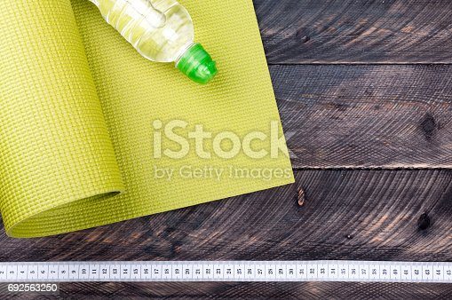 637596492istockphoto Yoga mat, water bottle and measuring tape on a wooden background. Equipment for yoga. oncept  healthy lifestyle 692563250