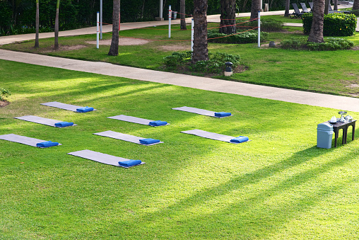 Yoga mats and towels on the green grass in the park