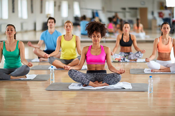 Yoga meditation group Yoga meditation group at fitness center lotus position stock pictures, royalty-free photos & images