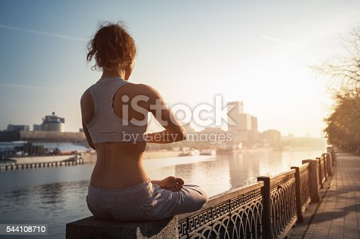 Young Woman Doing Yoga Meditation Exercise Sitting in Lotus Position Near River. Urban Scene. Stock Photo.