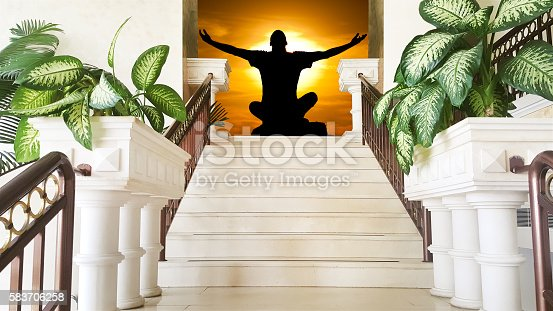 Yoga meditation in pose by man silhouette in a dramatic sky background.