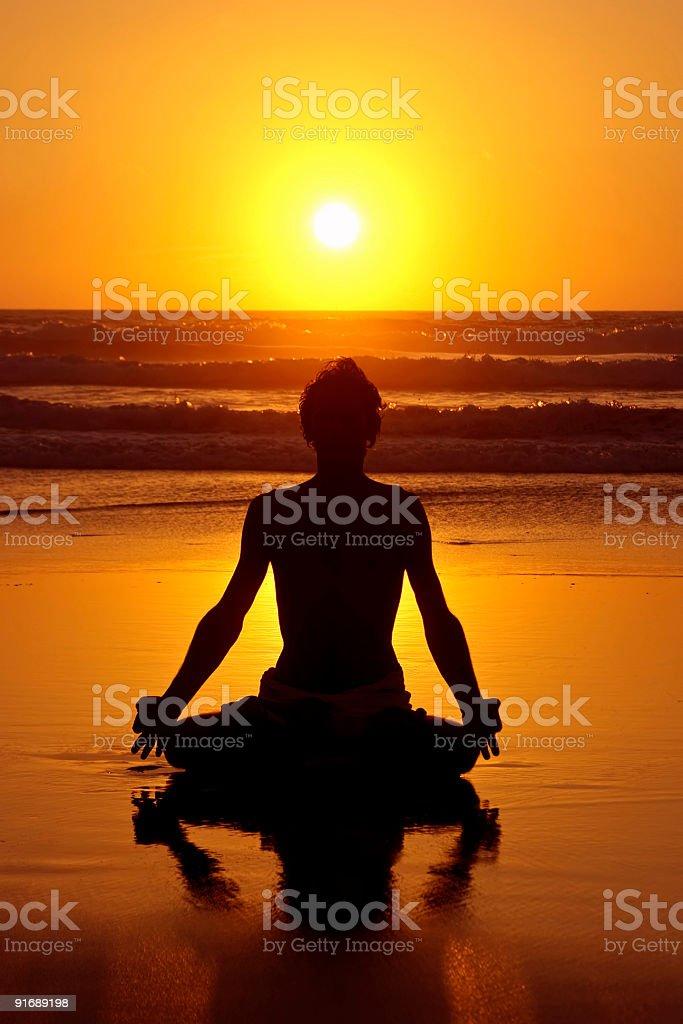 Yoga meditation on the beach at sunset royalty-free stock photo