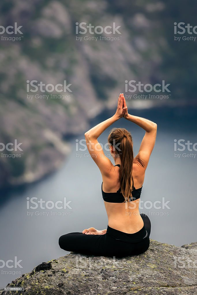 Yoga meditation posture on a cliff. Lysefjord - Norway stock photo