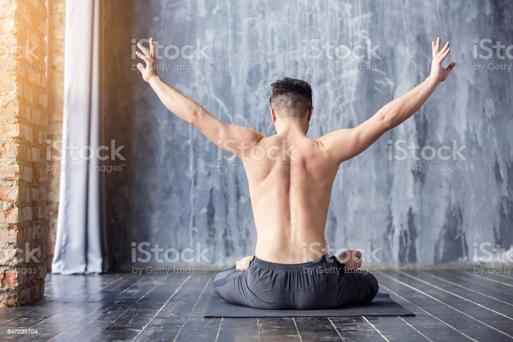 Young caucasian yoga master practicing yoga near a window. Yogi men...