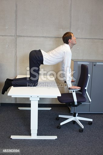 511849865 istock photo yoga office - man practicing at workplace 483363594