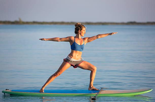 yoga von einem stehpaddelbrett - stehpaddeln stock-fotos und bilder