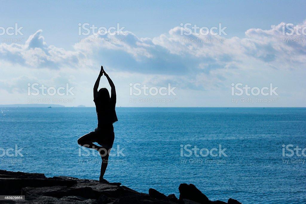 Yoga on beach - Tree Pose stock photo